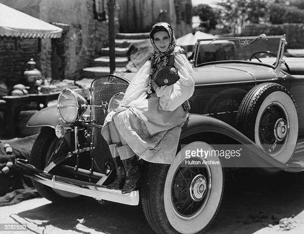 Raquel Torres the screen name of Paula Marie Osterman a Metro Goldwyn Mayer player sitting on the wheel arch of her car