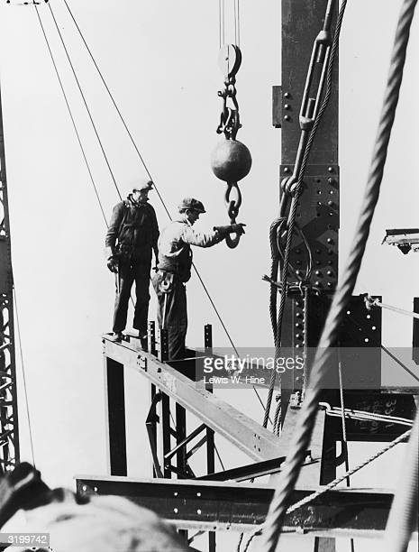 Two male construction workers using a hoisting ball while standing on a steel girder on top of the mooring mast of the Empire State Building in New...