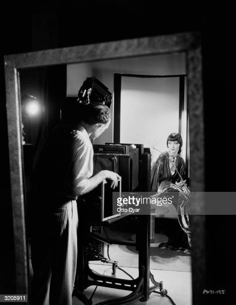 A reflection in a mirror shows Paramount photographer Otto Dyar taking a studio portrait of ChineseAmerican film star Anna May Wong