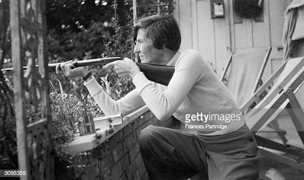Alix Strachey taking aim on the verandah at Ham Spray Wiltshire the home of Frances and Ralph Partridge