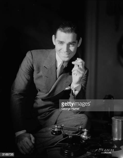 American actor Clark Gable leaning on his desk having a cigarette Nominated three times for the Academy Award for Best Actor he won it only once for...