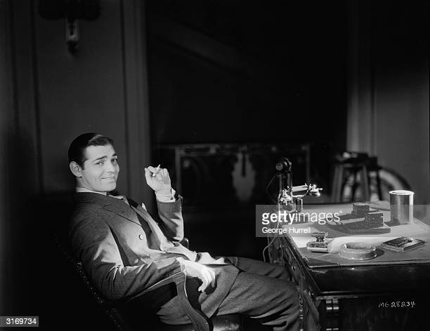 American actor Clark Gable sitting at his desk having a cigarette