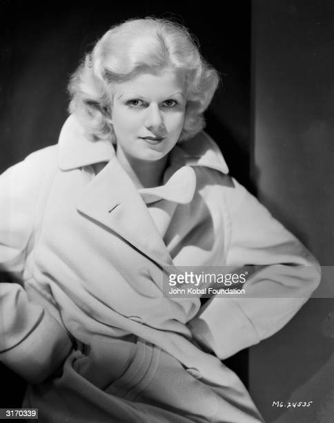 American actress and sex symbol Jean Harlow wearing a trenchcoat