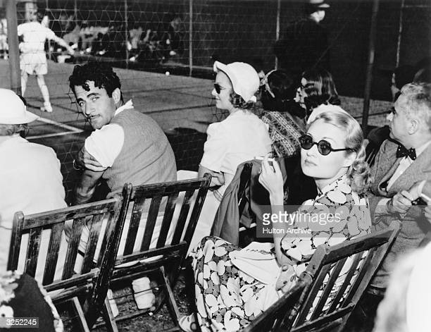 American actress Constance Bennett sitting with Mexican leading man Gilbert Roland at Beverly Hills Tennis club