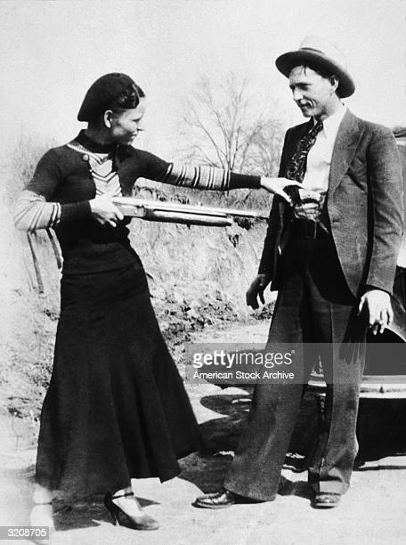 American criminal Bonnie Parker aims a shotgun at her partner, Clyde Barrow while clowning beside an automobile, early 1930s.