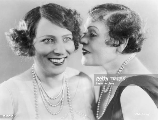 American film actress Polly Moran whispering to a friend