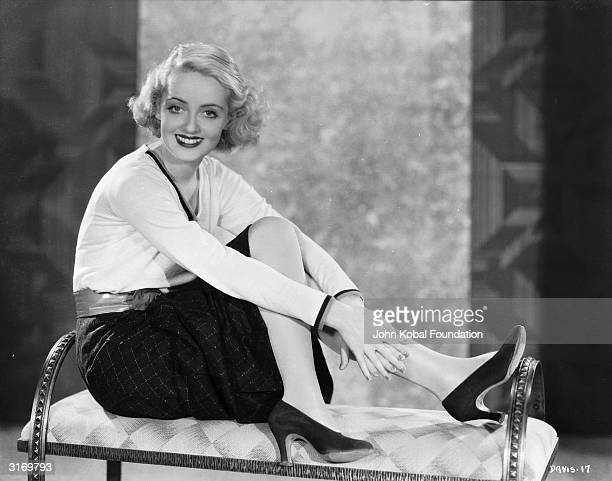 American film star Bette Davis wearing high heels and a winning smile