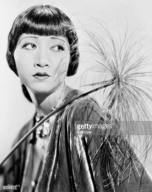ChineseAmerican film star Anna May Wong poses with a dried plant