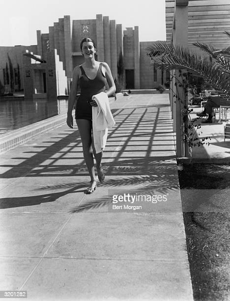 Full-length image of actor and sports champion Sandra Shaw , wearing a bathing suit, smiling while walking on the deck of a swimming pool at the...
