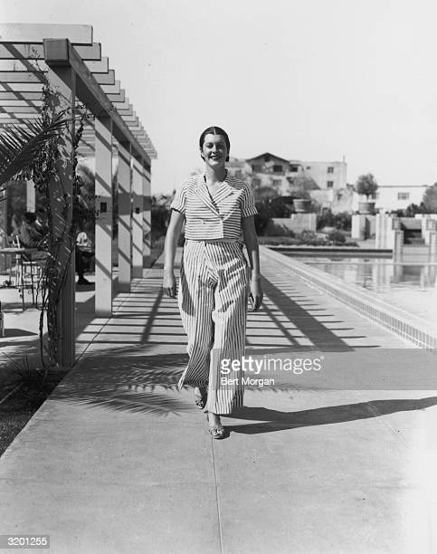 Full-length image of actor Sandra Shaw , smiling while walking on the deck of a swimming pool in a striped jacket and matching trousers at the...