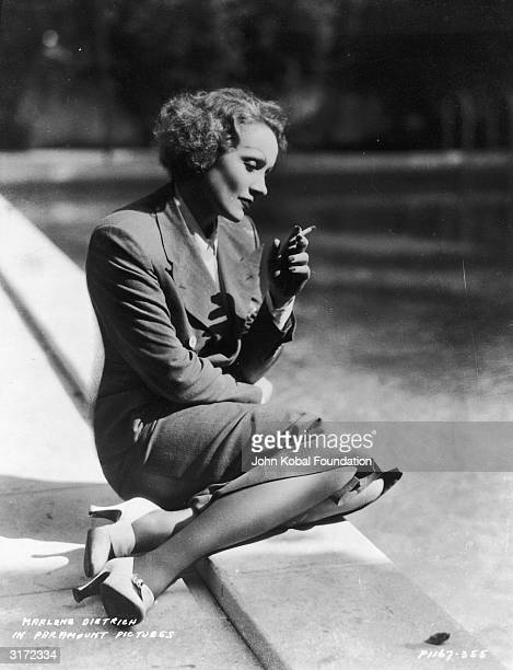 German born American actress Marlene Dietrich kneeling by a lake smoking a cigarette in a double breasted suit