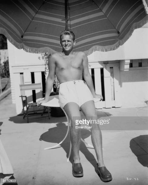 Hollywood actor Douglas Fairbanks Jr the son of Douglas Fairbanks lounges barechested beneath the shade of an umbrella