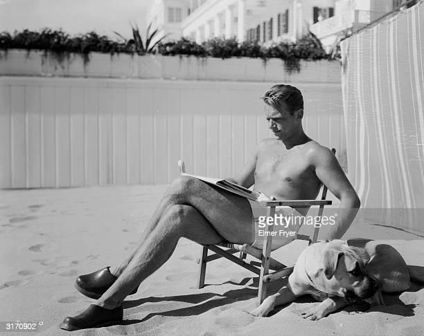 Hollywood actor Douglas Fairbanks Junior the son of Douglas Fairbanks lounges barechested on a deckchair on the beach