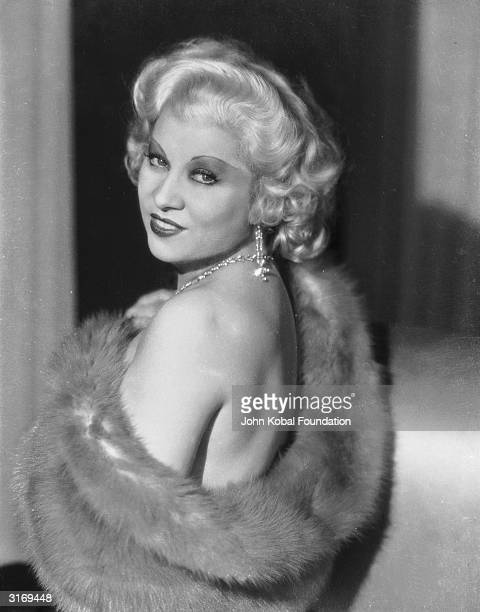 Mae West bares her shoulder from underneath a fur stole.