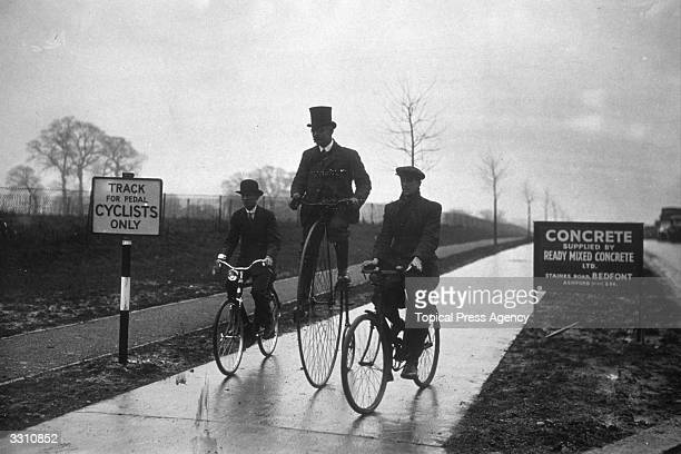 Three men on various styles of bicycle including a Penny Farthing riding down the newly opened Belisha cycling path between Hanger Lane and Greenford...