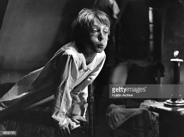Young actor Robert Lynen blows out a candle in a scene from the French film 'Poil De Carotte' directed by Julien Duvivier