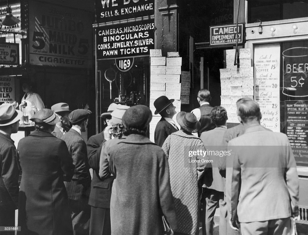 A crowd of unemployed people gathers to look at job postings outside of an employment agency on Sixth Avenue in New York City.