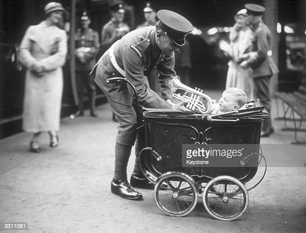A member of the Grenadier Guards seen here encouraging his baby son to play the trumpet before he leaves for the International Festival of Music in...