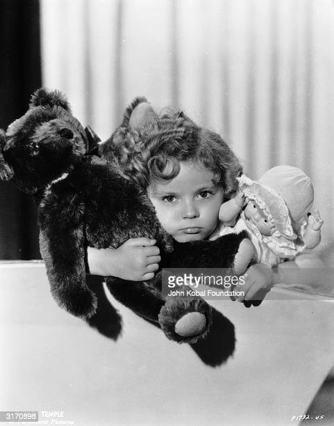 Already a Hollywood child star young Shirley Temple clutches a teddy bear and a doll like any normal girl her age