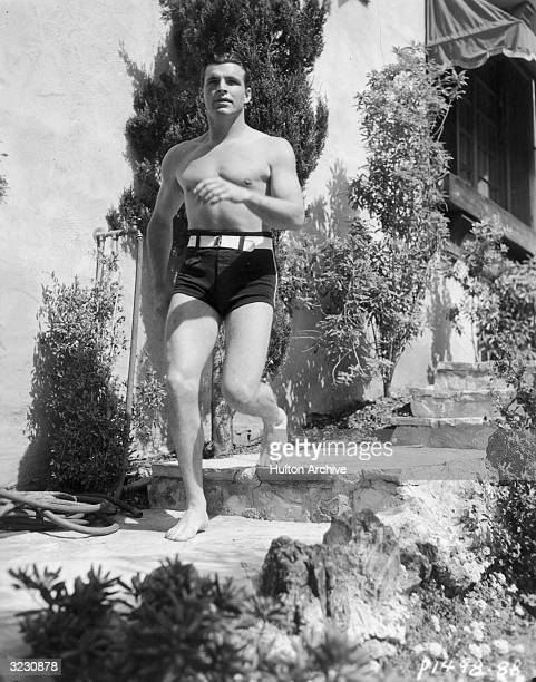 American actor and Olympic swimming champion Buster Crabbe wearing swimming trunks with a white belt running down stone steps outdoors