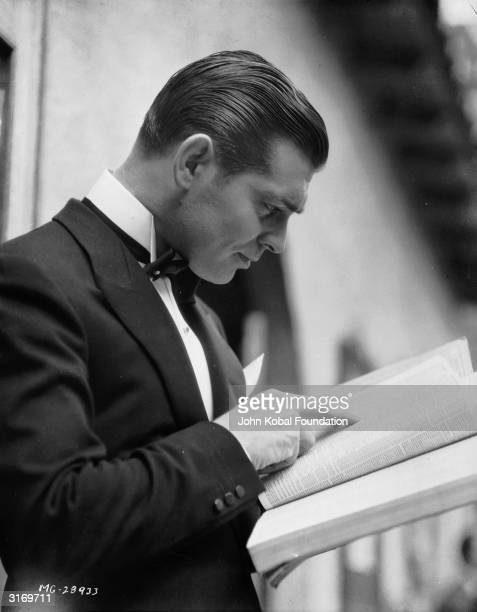 American actor Clark Gable wearing a dinner jacket and looking through a directory