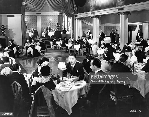 American comic actor Jack Oakie at a dinner dance in a scene from the Paramount film 'Night Life'