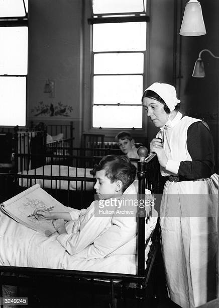 An interior view of University College Hospital showing nurses at work in one of the wards