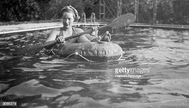 An unknown woman relaxing in the swimming pool at Ham Spray Wiltshire home of Frances and Ralph Partridge