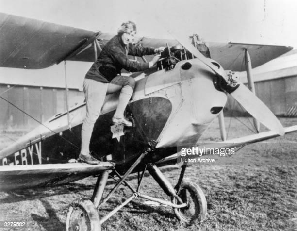 British aviator Amy Johnson climbing into her biplane