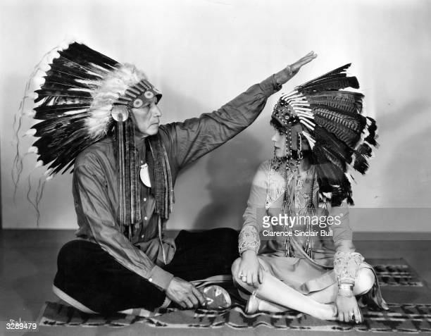 Chief Bigtree performs a traditional ceremony of well wishing on Dorothy Janis the MGM feature player who is of Cherokee extraction