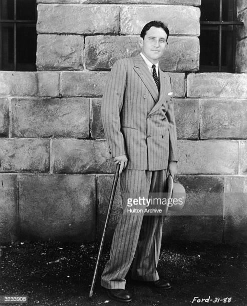 Full-length, outdoor portrait of American actor Spencer Tracy wearing a pinstriped, double-breasted suit, holding a cane and a hat.