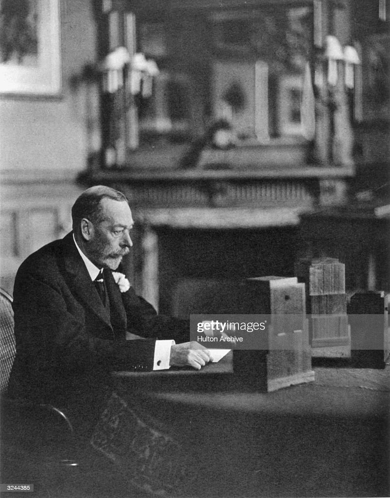 George V (1865 - 1936), King of Great Britain preparing to give a radio broadcast from a room at Sandringham.