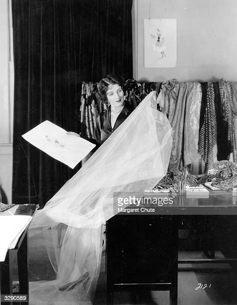 Gertrude Olmsted the Metro Goldwyn Mayer player looks at the material and a sketch of a gown she will be wearing in her next picture