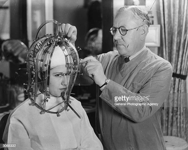 Hollywood cosmetics expert Max Factor takes precise measurements of a young woman's head and face with a contraption like an instrument of torture