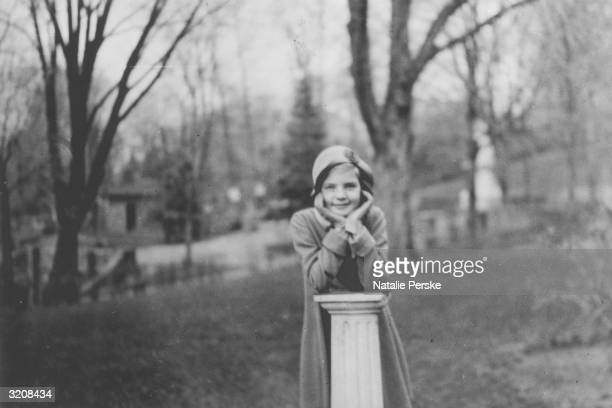 Portrait of 9 yearold Lauren Bacall leaning on a column outdoors at Highland Manor private girls' school TarrytownontheHudson New York