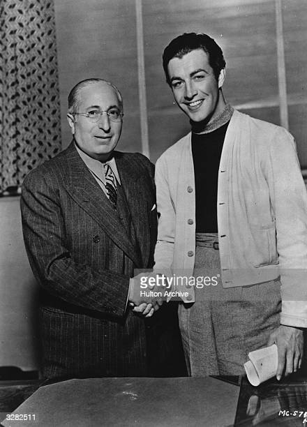 Robert Taylor the screen name of Spangler Arlington Brugh the American leading man who was contracted to Metro Goldwyn Mayer shaking hands with an...
