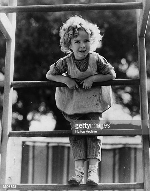 Shirley Temple the American child star at five years of age standing on her climbing frame at home