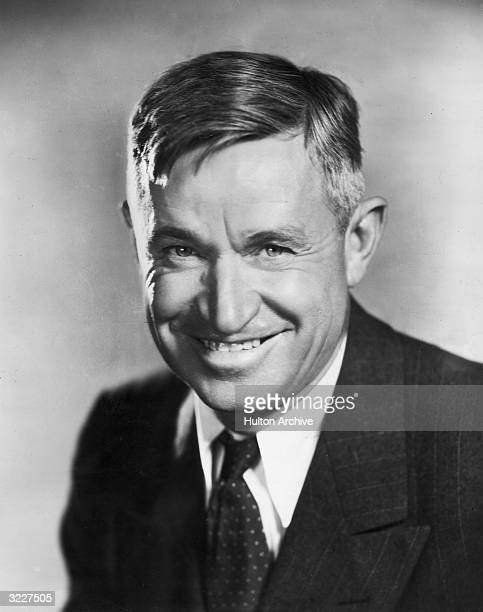 Studio portrait of American humorist and actor Will Rogers smiling in a jacket and tie