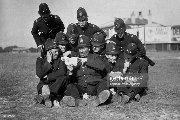 A group of policemen study the form trying to spot a winner at the Epsom Derby