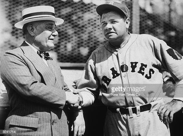 American baseball player Babe Ruth wearing a Boston Braves uniform shakes hands with Jacob Ruppert owner of the New York Yankees Ruth was a player...