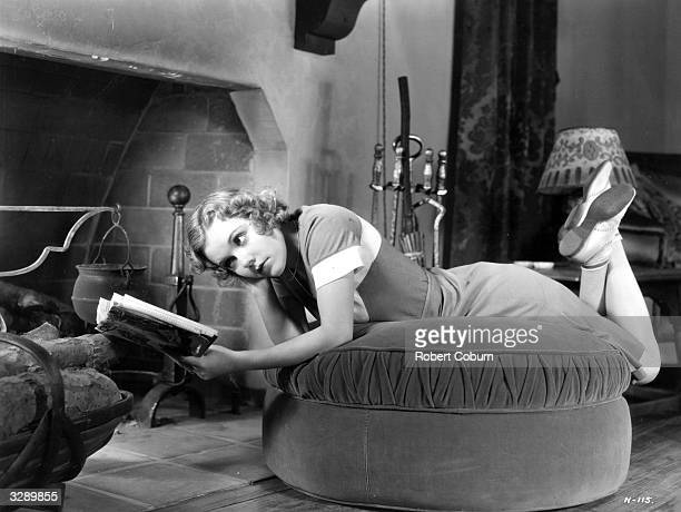 Dorothy Lee the American leading lady of the 30's Dorothy is so absorbed in her book that she has not noticed that the fire has gone out