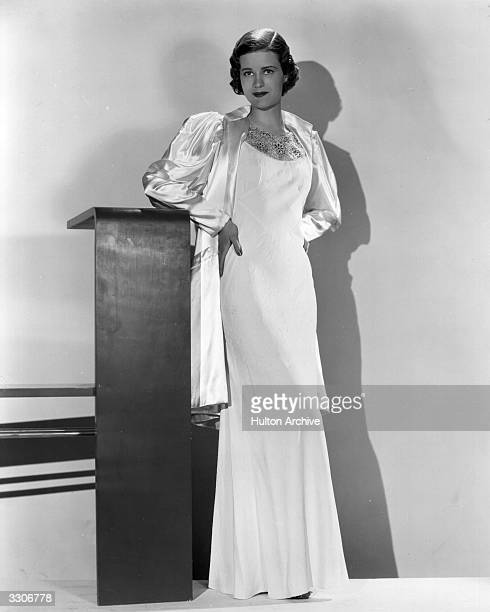 Elizabeth Young the Paramount player of the 30's is wearing a wrap and frock in white satin and crepe The coat has tailored wide shoulders made of...