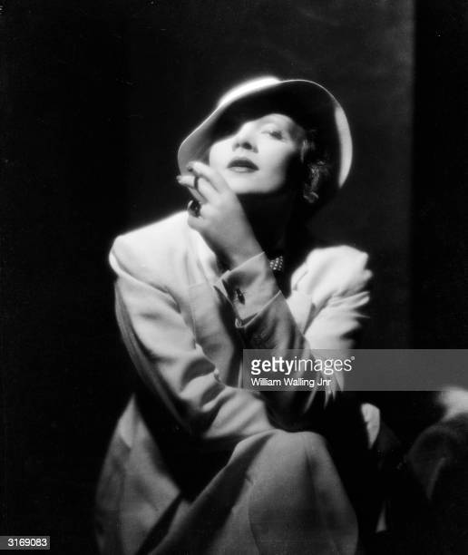 Film star Marlene Dietrich wearing a soft pull-on hat and smoking a cigarette.