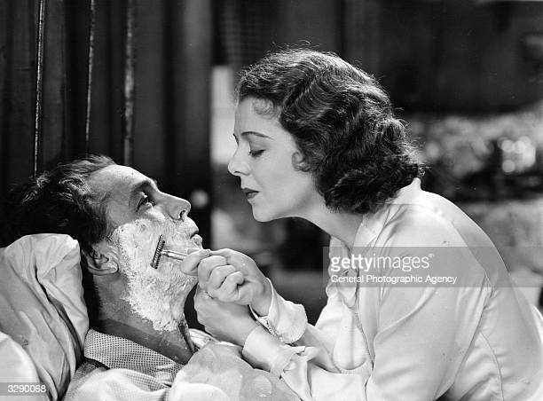 Janet Gaynor is shaving Charles Farrell in the musical film 'Change Of Heart' directed by Albert S Rogell for Republic
