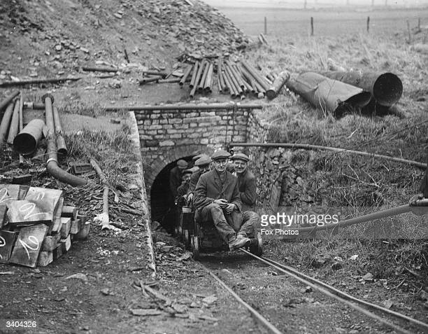 Miners emrge back into the light from a coal mine on a miniature railway carriage