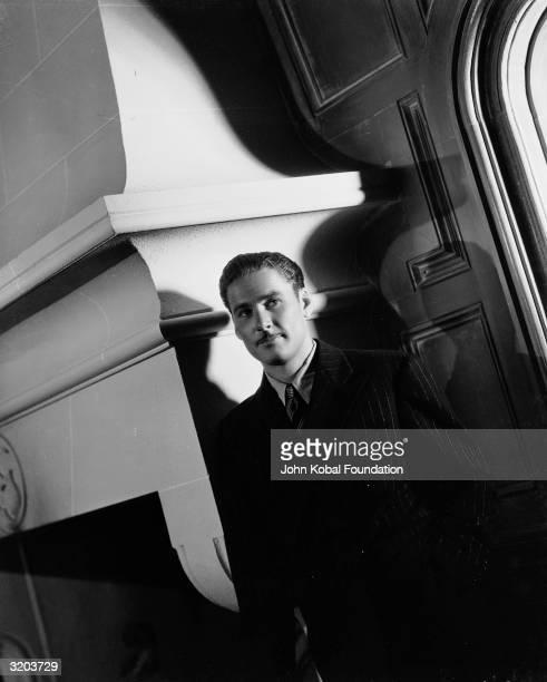 Tasmanian film star Errol Flynn standing next to a grand fireplace