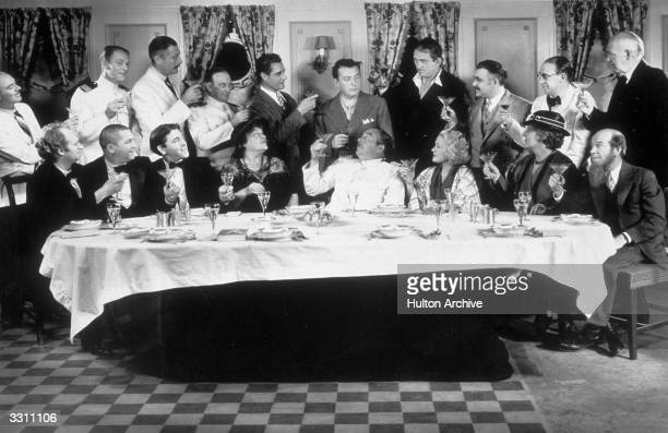 The cast of the Columbia nautical comedy thriller 'The Captain Hates The Sea' making a toast to their director Lewis Milestone