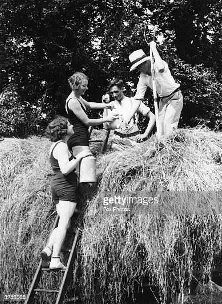 Two women in swimsuits providing refreshments for farm labourers during haytiming