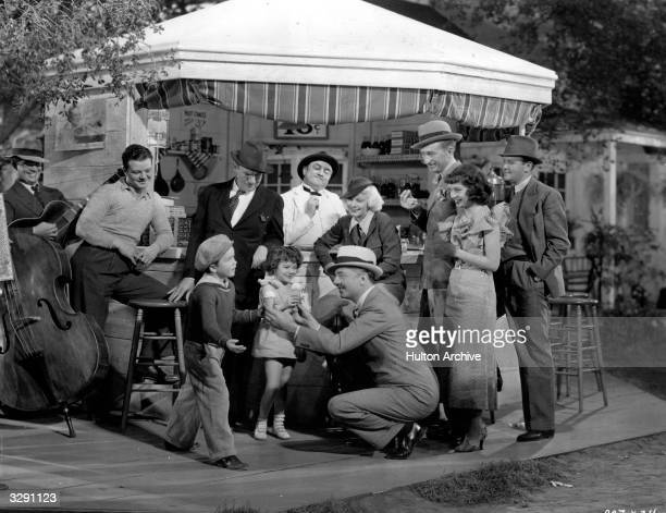 William Powell the Metro Goldwyn Mayer leading man is giving icecream cones to Dickie Jones and Jeanie Gunn the two child actors for their good...