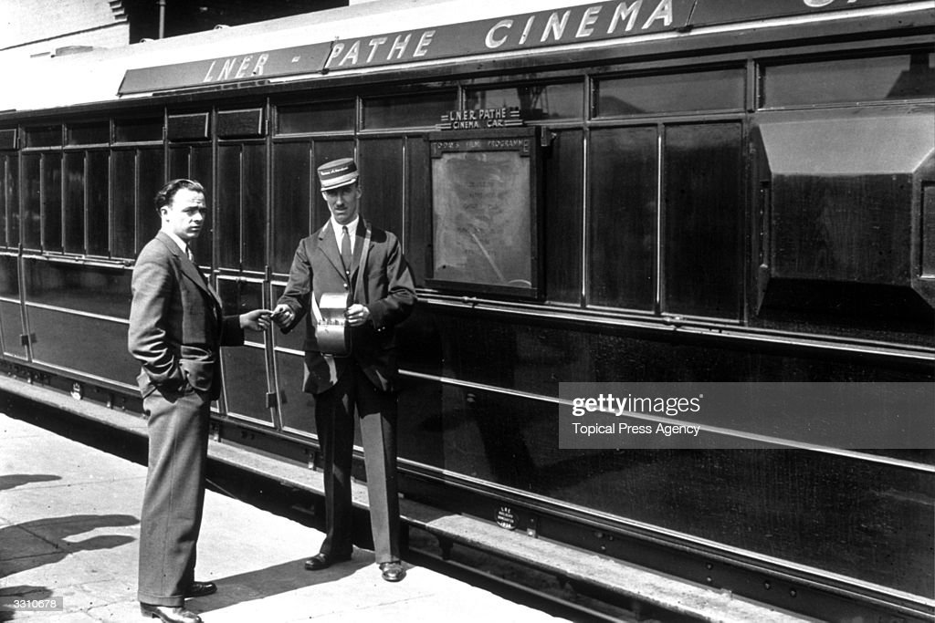 A cinema attendant giving a ticket to a passenger for the Pathe cinema car, which ran on LNER trains.